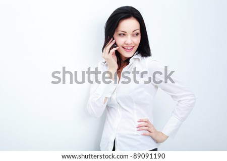 Cheerful business woman conversing on mobile phone - stock photo