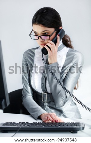 Cheerful business woman conversing on  phone