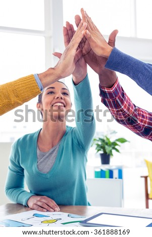 Cheerful Business woman doing high five with team in creative office - stock photo