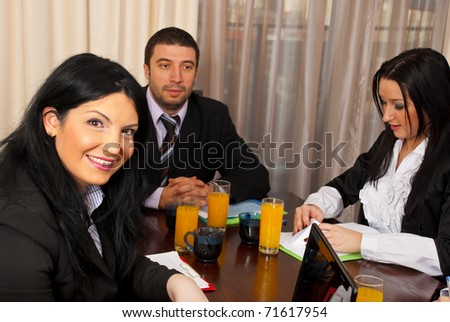 Cheerful business woman looking at camera and having a business meeting - stock photo