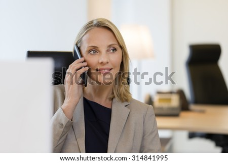 Cheerful business woman on mobile phone at office - stock photo
