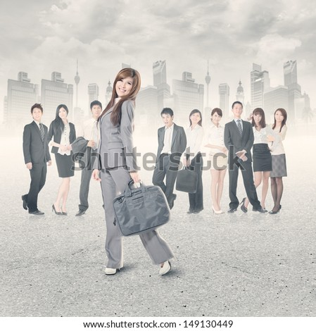 Cheerful business woman stand and look at you with her team.