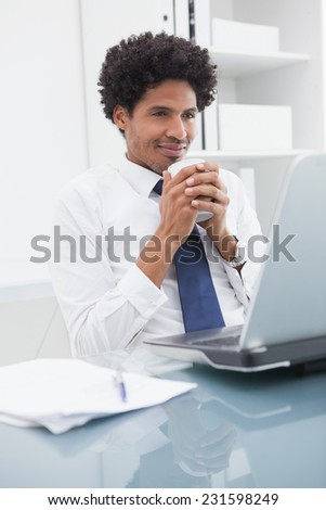 Cheerful businessman enjoying hot drink in the office