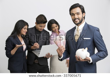 Cheerful businessman holding piggy bank with his busy colleagues on white background. - stock photo