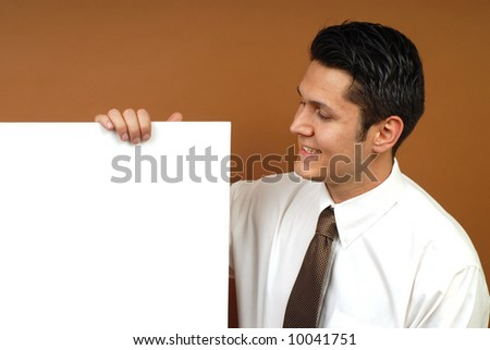 Cheerful businessman holding poster copy space; easily extendable for banner size