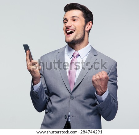 Cheerful businessman holding smartphone and celebrating his success over gray background - stock photo