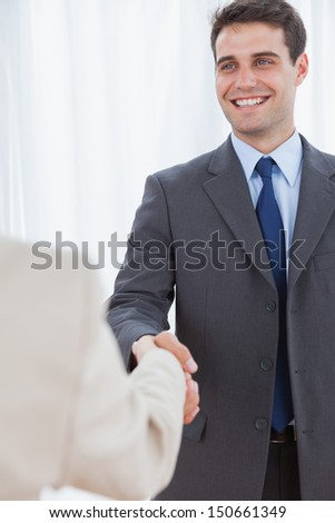 Cheerful businessman in bright office shaking hands with his new workmate - stock photo