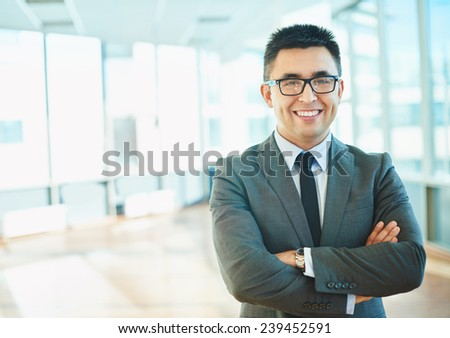 Cheerful businessman in formalwear keeping his arms crossed - stock photo