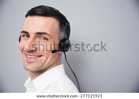 Cheerful businessman in headphones standing over gray background and looking at camera - stock photo