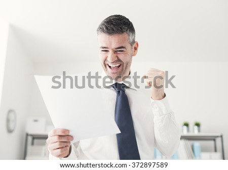 Cheerful businessman in the office receiving good news, he is holding a contract document and raising his fist - stock photo