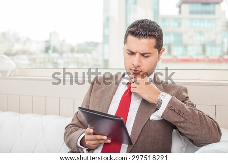 Cheerful businessman is sitting and holding a laptop in his hand. He is looking at it with seriousness and touching his chin pensively. Copy space in left side - stock photo
