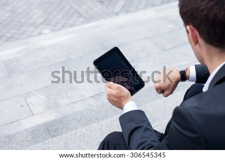 Cheerful businessman is sitting on steps outdoors and using a tablet. He is looking at his watch with concentration. He has a meeting today. Focus on his back and copy space in left side - stock photo