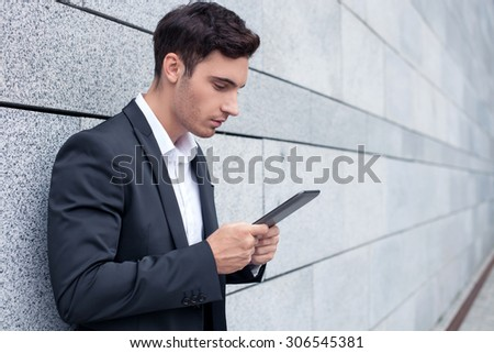 Cheerful businessman is standing and leaning on wall. He is using a tablet for work. The guy is looking at the technology seriously. Copy space in right side - stock photo