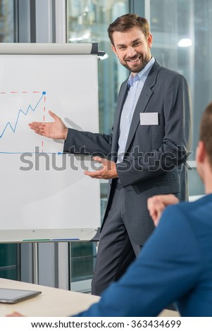Cheerful businessman is standing near a board and explaining his colleague his ideas. He is pointing arm on diagram and smiling. The man is sitting at desk interest - stock photo