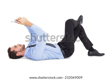Cheerful businessman lying on floor using tablet o white background - stock photo