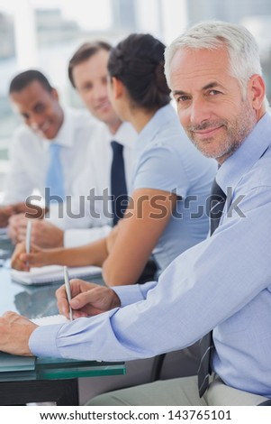 Cheerful businessman posing in the meeting room while colleagues are working behind - stock photo