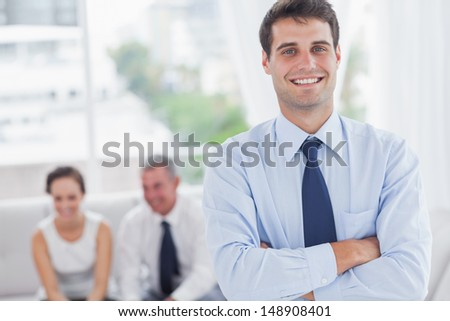 Cheerful businessman posing while his colleagues are working in cosy meeting room