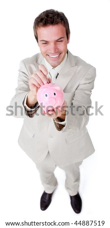 Cheerful businessman saving money in a piggybank against a white background - stock photo
