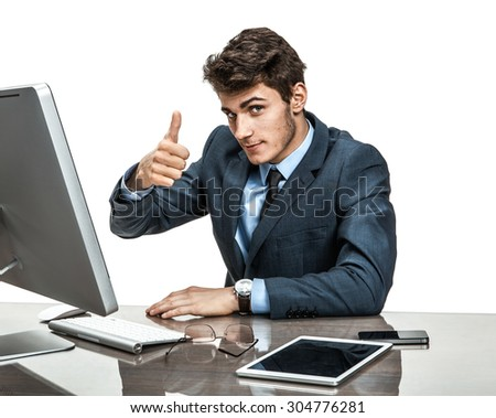Cheerful businessman showing thumbs up success sign / modern businessman at the workplace working with computer - stock photo