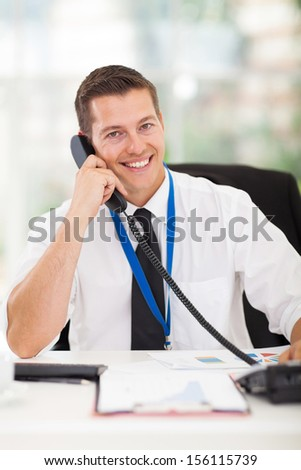 cheerful businessman talking on phone in the office