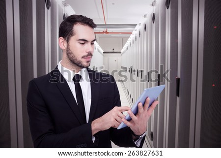 Cheerful businessman touching digital tablet against data center