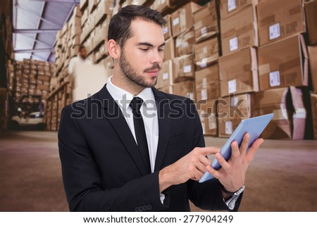 Cheerful businessman touching digital tablet against worker with fork pallet truck stacker in warehouse - stock photo