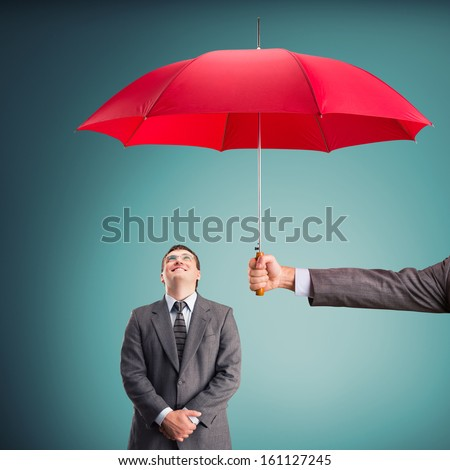Cheerful businessman under an umbrella - stock photo