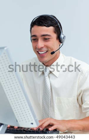 Cheerful businessman using headset working at a computer - stock photo