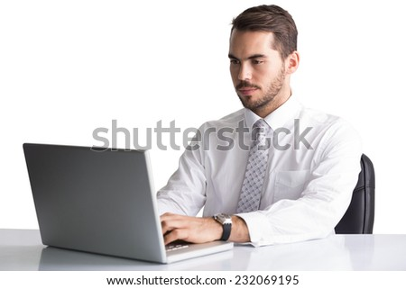 Cheerful businessman using laptop at desk on white background - stock photo