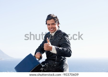Cheerful businessman with the thumb up while holding a briefcase - stock photo