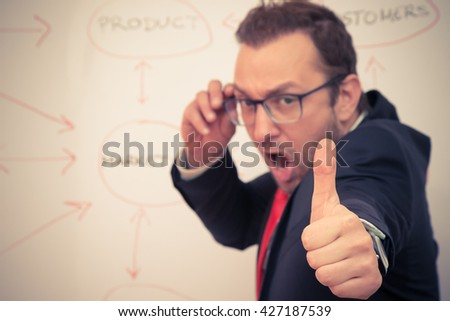 Cheerful businessman with thumbs up gesture in front of the white board with flowchart. Selective focus. Business success concept.  - stock photo