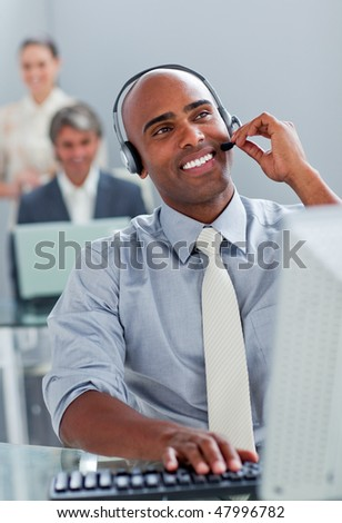 Cheerful businessman working at a computer with headset on in the office