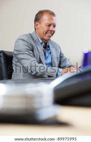 Cheerful businessman working on laptop at office - stock photo