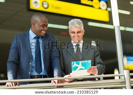 cheerful businessmen holding air ticket at airport - stock photo