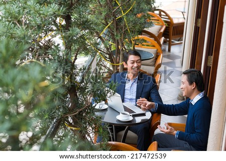 Cheerful businessmen using laptop at the meeting - stock photo