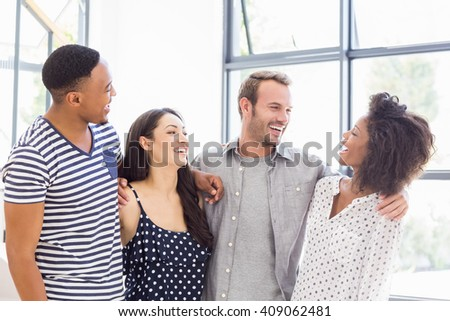 Cheerful businesspeople interacting and smiling in office - stock photo
