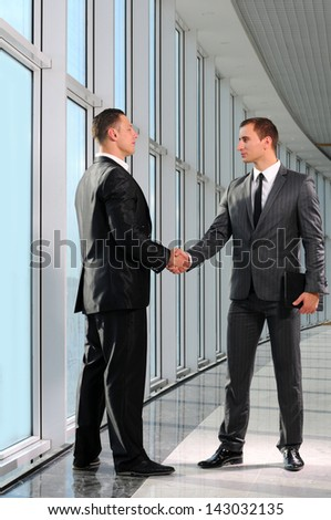 Cheerful businesspeople, or businessman and client, handshaking - stock photo