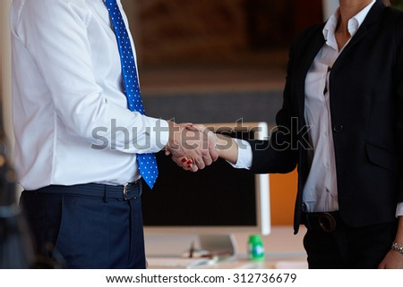 Cheerful businesspeople, or businesswoman and client handshaking at office - stock photo