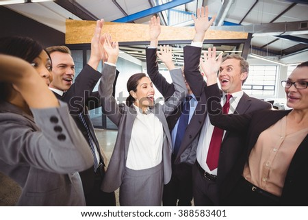 Cheerful businesspeople raising hands in office - stock photo