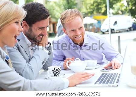 Cheerful businesspeople using laptop together at sidewalk cafe - stock photo