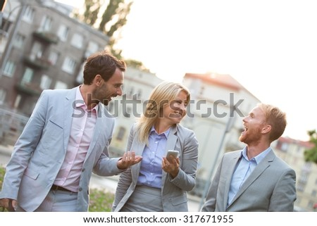 Cheerful businesspeople walking in city - stock photo