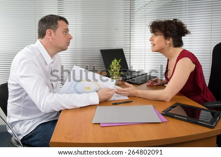Cheerful businesspeople working with laptop at office - stock photo