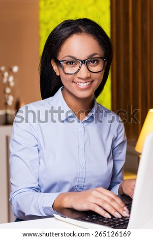 Cheerful businesswoman. Attractive young African woman working on laptop and smiling while sitting at her working place - stock photo