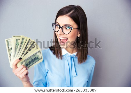 Cheerful businesswoman holding bills of dollar over gray background. Wearing in blue shirt and glasses. - stock photo