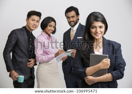 Cheerful businesswoman holding tablet  with her colleagues on white background. - stock photo