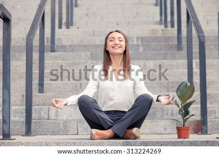 Cheerful businesswoman is sitting on steps near her office in lotus position. She closed her eyes with enjoyment. The lady is relaxing and smiling. The flowerpot is situated near her - stock photo