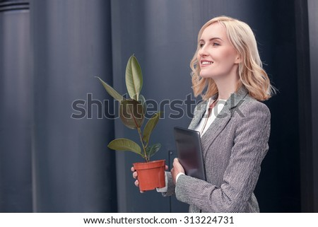 Cheerful businesswoman is standing and smiling. She is holding a plant and a laptop. The blond lady is looking forward proudly. Copy space in left side - stock photo