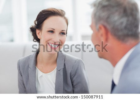 Cheerful businesswoman listening to her workmate talking in bright office - stock photo