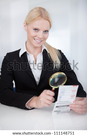 Cheerful businesswoman looking at check trough the loupe - stock photo