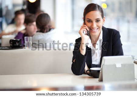 Cheerful businesswoman on a coffee break talking on the phone in a cafe
